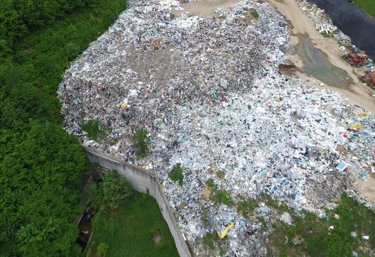 Може да видите как отстрана на бетонната ограда сметището за битови отпадъци буквално прелива